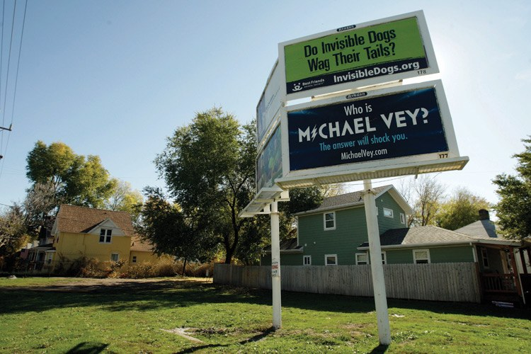 A four-panel billboard occupies a vacant lot where neighbors want to create a park to honor a slain policeman.