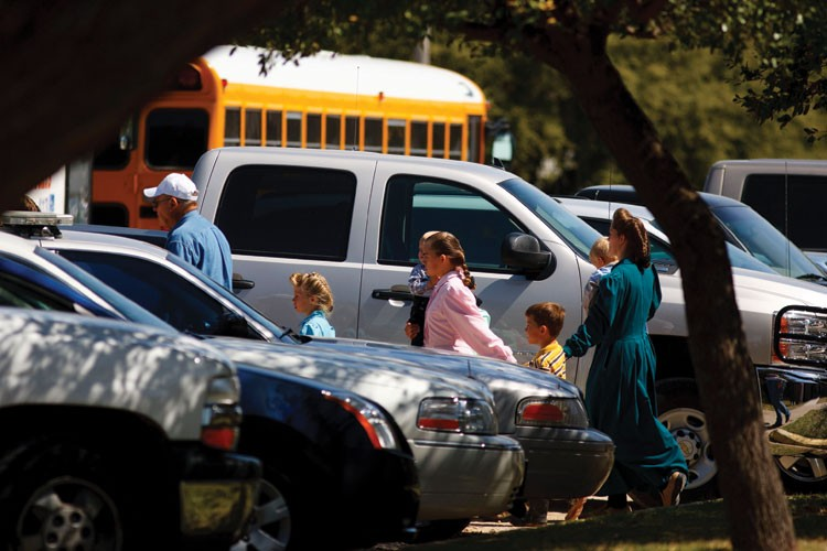 FLDS women and children are escorted by Texas Child Protective Services workers to waiting buses after they were removed from the sect's YFZ Ranch compound in April 2008.