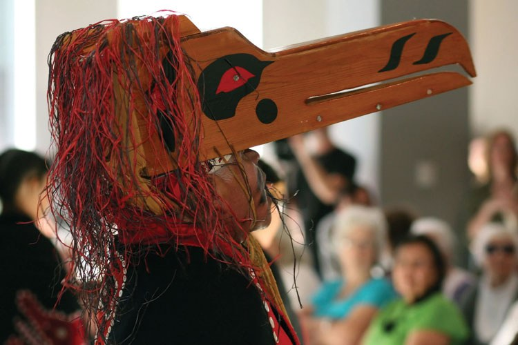A Quileute tribal member performs a raven dance (above) in conne