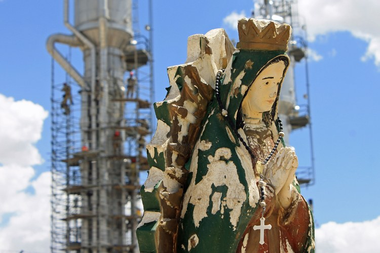 A Virgin Mary statue in a cemetery near Bloomfield, N.M., that is nestled up against a natural gas processing plant.