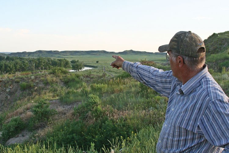 Mark Fix shows the area on his Tongue River ranch where a new rail line is proposed that would haul coal to the coast for export.