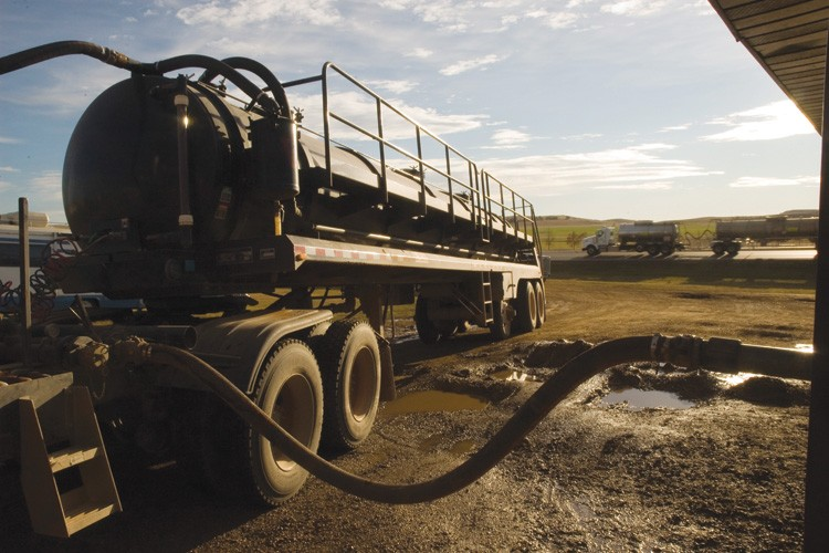 A water truck  fills up at a depot near Watford City, North Dakota, while another heads back to a well site that will need up to 800 such loads for fracking.