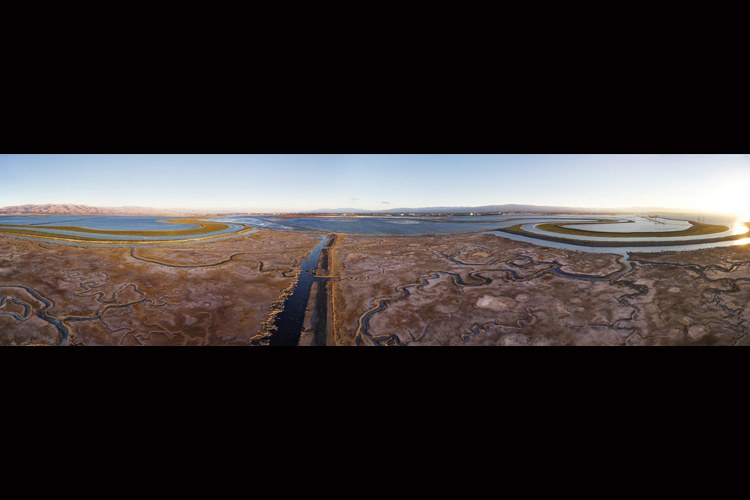 Panorama of Salt Pond A6, taken in 2010 before the area was breached as part of the South Bay Salt Pond Restoration Project. Today, the area has accumulated sediment and looks like a natural mudflat. The image was created by stitching together 12 wide-angle frames taken by a camera at 150 feet, suspended from a kite, and is part of the Hidden Ecologies Project, http://bit.ly/NYMgAq.