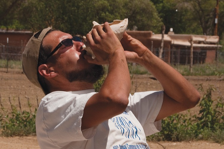 "Miguel Santistevan, whose ancestors were conquistadors and members of the Taos Pueblo, works with Taos youths to save his ""lost community."" Santistevan blows on a conch shell to call a rotation of Sangre de Cristo Youth Ranch participants to their next tasks."