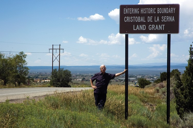 Ernest Romero stands at a sign marking the entrance to one of the Taos Valley's traditional land-grant areas, now dotted with development, some of which is tied up in legal battles over property rights.