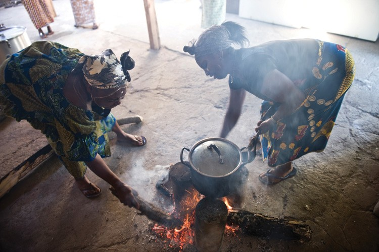 Alice Toe and Cynnomih Tarlesson, in traditional African dress, stoke a cooking fire.