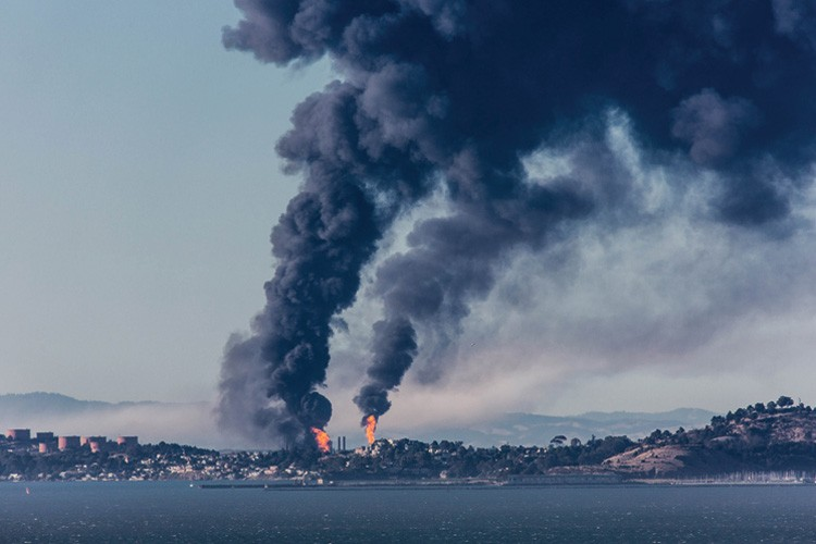 Flames and plumes of smoke rise from the Chevron refinery in Richmond, California, after an explosion last month. Nearby residents were warned to stay inside, but more than 14,000 were eventually treated at nearby hospitals.