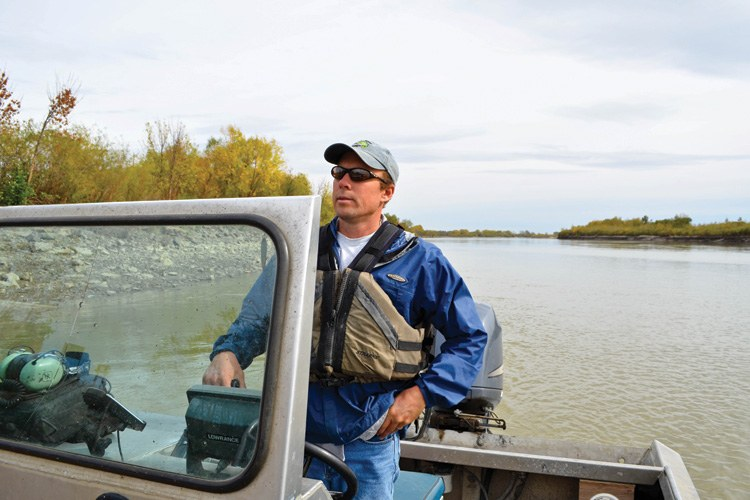Fisheries technician Dave Fuller pilots a boat on the Upper Missouri River, keeping tabs on the fewer than 150 wild pallid