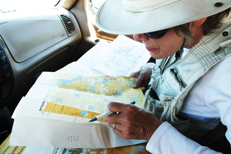 Peggy LeMone consults land ownership and geological maps at another intersection with Poison Spider Road, west of Casper, Wyoming, this July.