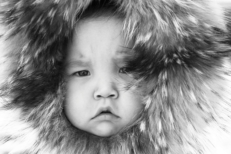 A Yup'ik child in a traditional fur parka on St. Lawrence Island, Al