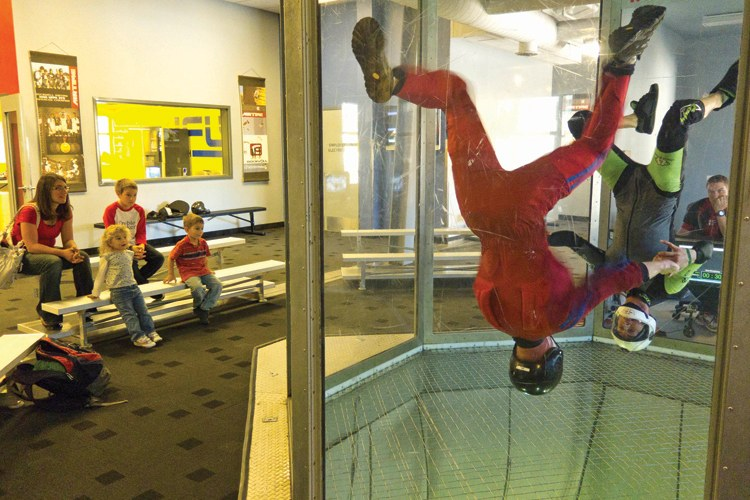 A young family watches indoor skydiving at the Salomon Center sports adventure complex in Ogden, Utah.