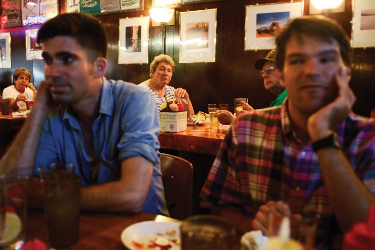 Patrons of Ray's Tavern in Green River, Utah, glance at a table full of Epicenter staff and volunteers, including visiting art fellows Justin Flood, left, and Rapha