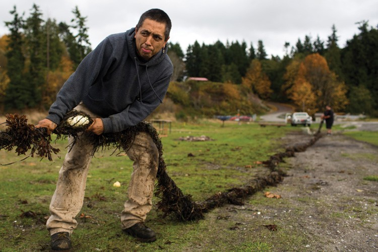 James Jones attempts to untangle and clean a fishing net on the Port Gamble S'Klallam Reservation in Washington. Like his father before him, Jones grew up fishing.