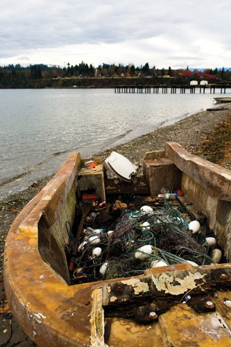 An old fishing boat on the shores of Port Gamble Bay, where the S'Klallam Tribe has fished for centuries. The old Puget Mill stands on the opposite shore.