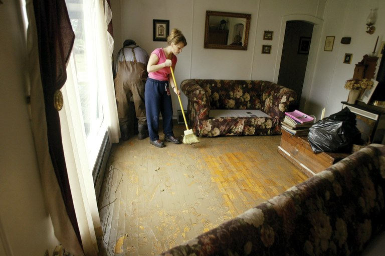 Berni Morgan tries to sweep mud off the floor of a Hamilton, Washington, home as she cleans up after a 2003 flood. The nearby Skagit River has flooded Hamilton five times in 22 years; an embattled insurance program run by FEMA has allowed the town to rebuild after the disasters.