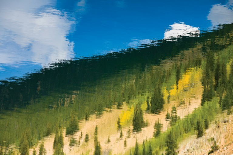 The abstracted image of an autumn landscape is reflected in a Colorado lake.