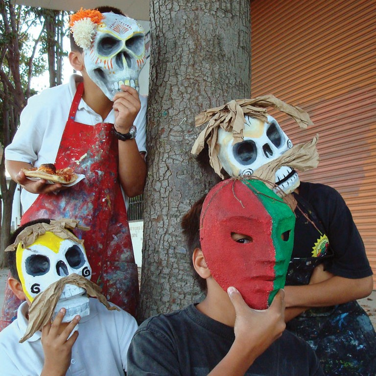 Young Day of the Dead festival participants model their masks at the National Steinbeck Center in Salinas, California.