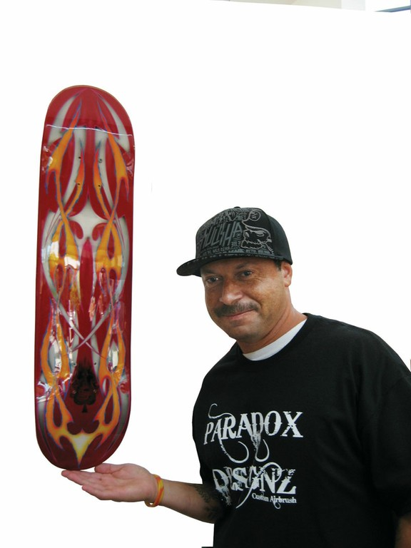 "Artist George Garcia with ""Fire and Desire,"" a piece in the Center's ""What the Deck?"" exhibit of skateboard art created by area residents, including some gang members."