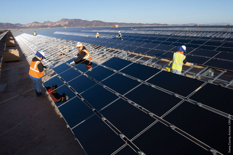 Workers at the Agua Caliente Solar Project install some of the three-and-a-half miles' worth of panels near Dateland, Arizona, about 50 miles west of Gila Bend.