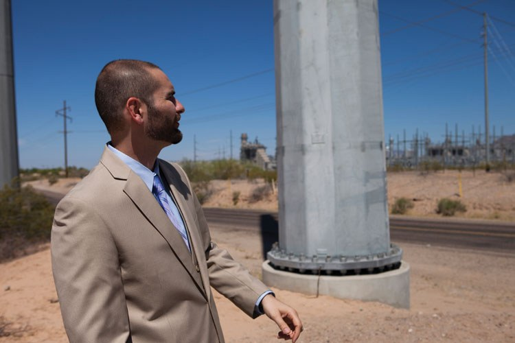 Eric Fitzer, planning and economic development director for Gila Bend, stands among the transmission lines within the city limits. Transmission is a key part of the equation, as Gila Bend increases its solar production and tries to sell the power, both instate and to neighboring California.