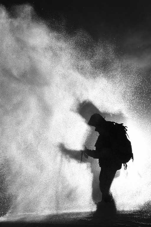A snowboarder is silhouetted on blowing snow in Big Cottonwood Canyon in the Wasatch Range.