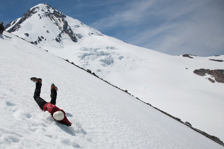 Outward Bound Instructor Sam Ecenia dives into alpine skills training on Mount Hood to start off the summer field season for Northwest Outward Bound School. Here he demonstrates the self-arrest, a technique to stop a fall on snow and ice.