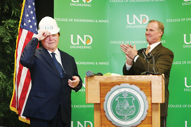 Oklahoma oil billionaire Harold Hamm, left, receives congratulations from University of North Dakota President Robert Kelley after Hamm's $10 million donation -- and the naming of the Harold Hamm School of Geology and Geological Engineering.