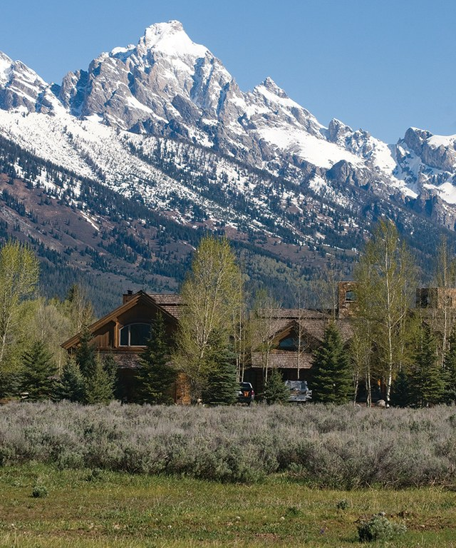 The peaks of the Teton Range loom over a house in the Solitude subdivision, which has some of the 	most expensive homes in Jackson, Wyoming.