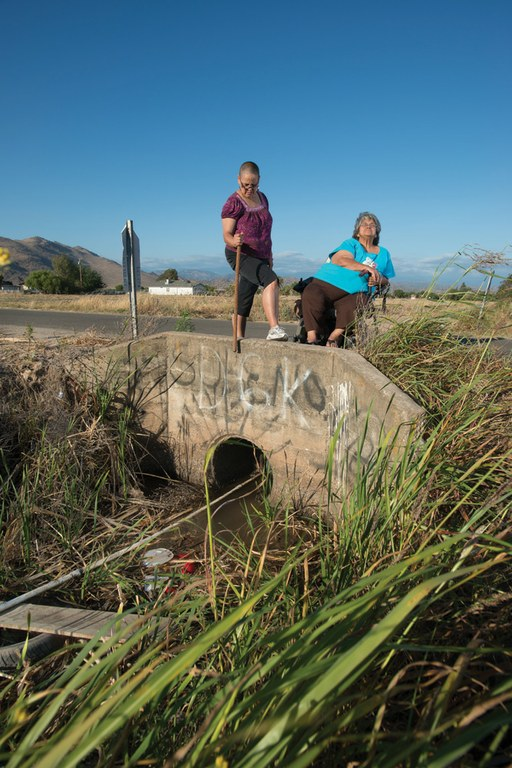 The water supply for the town of Seville, California, runs in a leaky PVC pipe through a trash-strewn ditch. Residents Becky Quintana and Delia Martinez buy bottled water for drinking.
