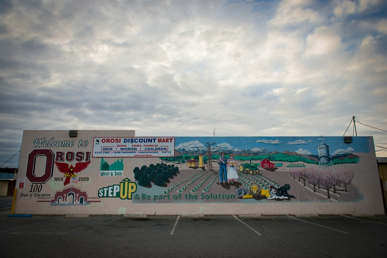 Morning clouds hang above a mural welcoming visitors to the Tulare County community of Orosi, California.