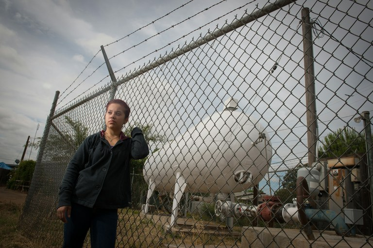 Jessica Sanchez, 20, next to her community's water tank in East Orosi.  Sanchez says her family spends an additional $30 to $40 a month on filtered water used for drinking, cooking and sanitizing baby bottles.