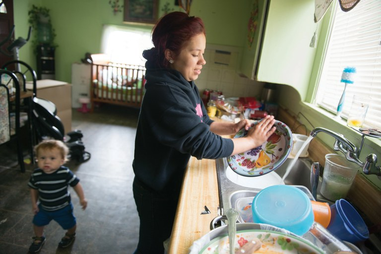 "Jessica Sanchez uses tap water to wash dishes in her East Orosi home while her son, Jordan, plays nearby. ""I definitely won't use this water to make formula,"" she says. ""But should I even give it to my dogs?"""