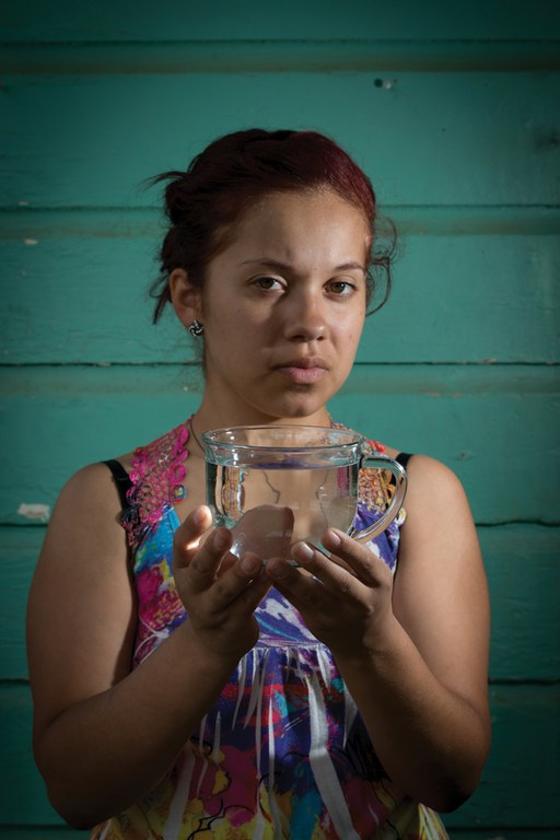 Central Valley water activist Jessica Sanchez holds a cup of undrinkable tap water at her East Orosi, California, home