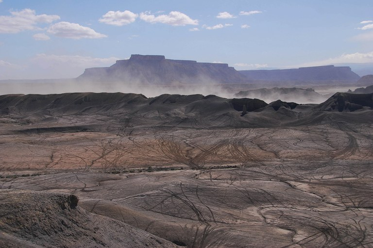 Dust rises near Factory Butte, an area just outside the San Rafael Swell that's a favorite of off-roaders and that SUWA and others hope to get designated as wilderness.