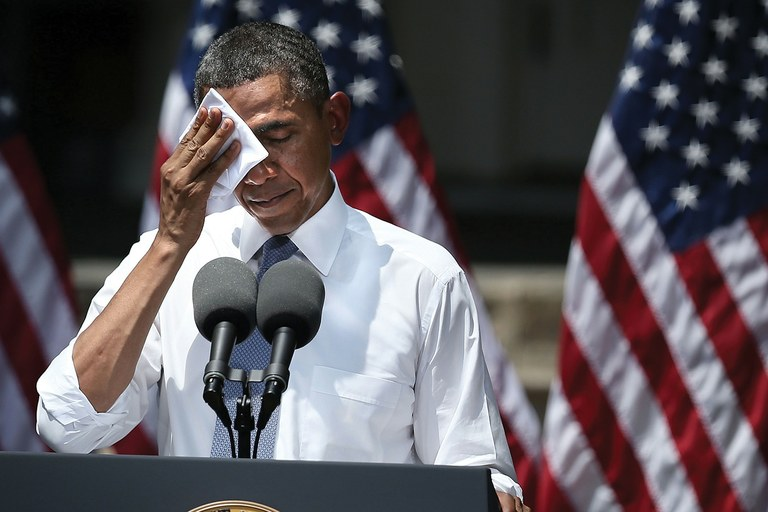 President Barack Obama wipes sweat from his brow dur