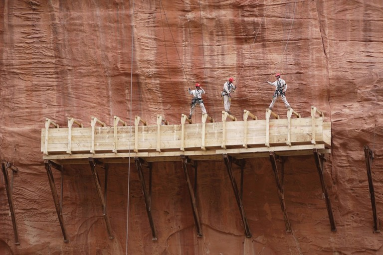 Reconstruction workers scale the canyon walls above the Hanging Flume.