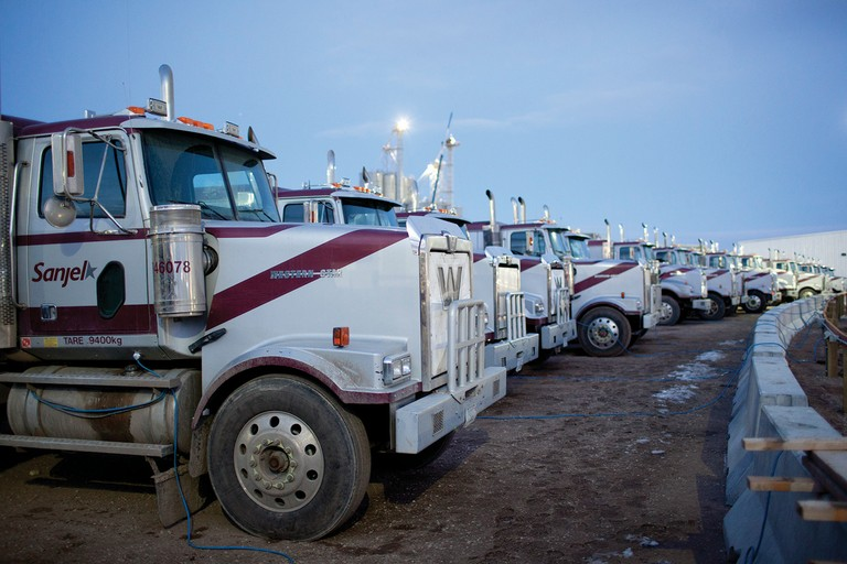Big rigs used to haul water line up in Williston, North Dakota.