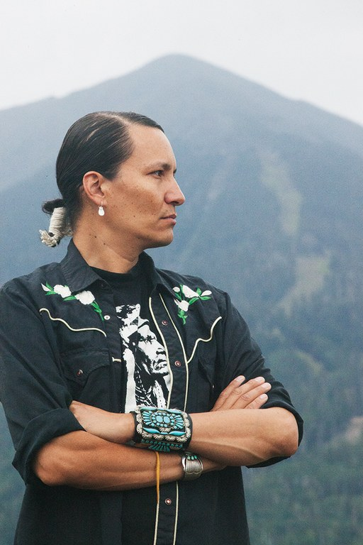 Diné activist Klee Benally with Arizona Snowbowl ski resort runs visible behind him.