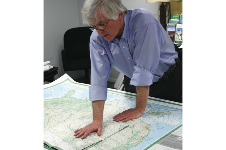 Dave Imus at a work table with the Essential Geography of the United States of America.