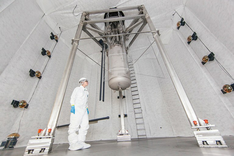 Physicist Rachel Mannino inspects the Large Underground Xenon dark matter detector newly installed in a water tank that shields it from background radiation.