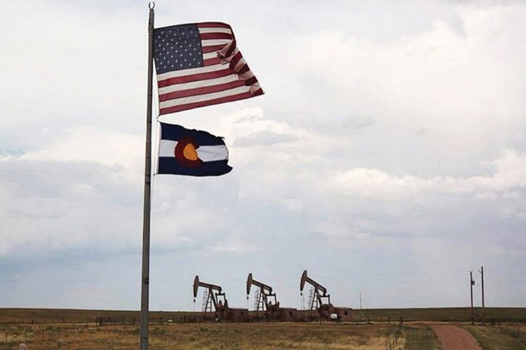 An American and a Colorado state flag fly alongside pumpjacks in Weld County, Colorado, one of 11 rural counties in Colorado with