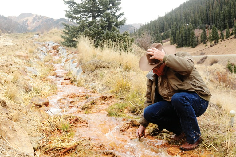 Steve Fearn dips his hand into drainage from the Elk Tunnel mine, where the BLM has built a limestone channel to treat acid mine drainage.