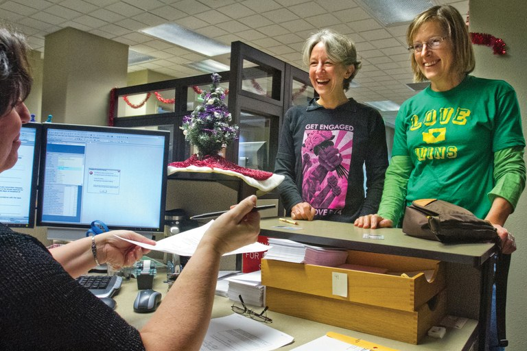Nina Tapscott, Chelan County recording and licenses manager, hands papers to Ana Maria Spagna and Laurie Thompson to review as they apply for a marriage license at the Chelan County Courthouse. They were the first same-sex couple to seek a marriage license in Chelan County, Washington.