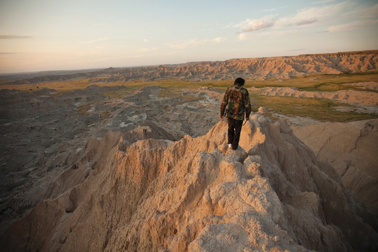Louie Brings Plenty carries sweet grass for burning while singing prayers on the sharp pinnacle 		overlooking the Stronghold in Badlands National Park. Louie is the whip carrier for a Lakota 		Tokala society, a traditional Warrior Society, and a member of NYM, the Native Youth Movement.