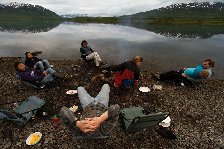 Researchers, including Daniel Schindler and his daughter, Luna, right, relax at camp after a day in the rivers and creeks of the Bristol Bay ecosystem, where roughing it includes, surprisingly, fresh mangos, front left.