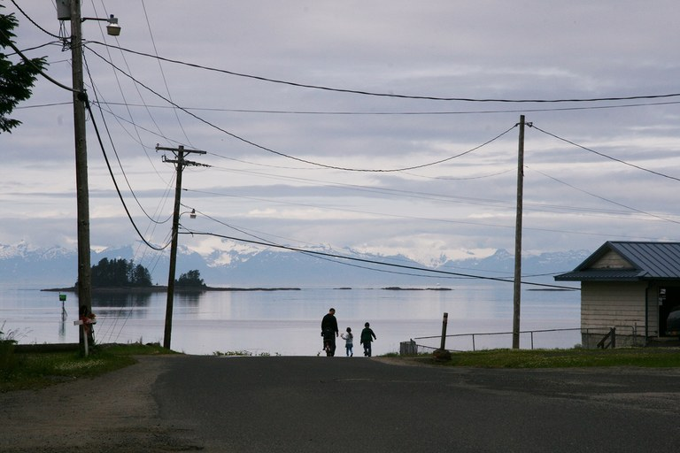 People walk along the waterfront in Kake, Alaska. The community, composed mostly of members