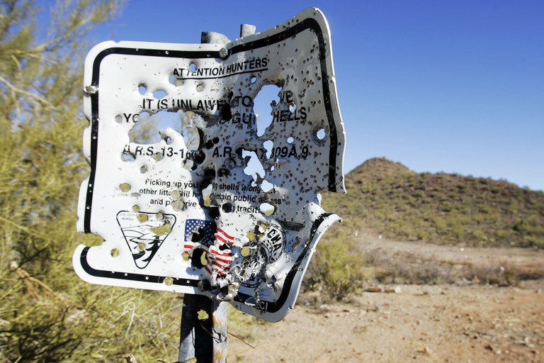 A BLM sign stating it is unlawful to leave shotgun shells behind is riddled with bullet holes in a wildcat shooting area in the Ironwood Forest National Monument. The BLM banned all recreational shooting in the monument in February.