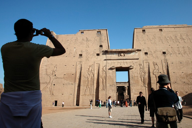 A tourist takes photographs of the main gate at the Temple of Horus in Edfu, Egypt.