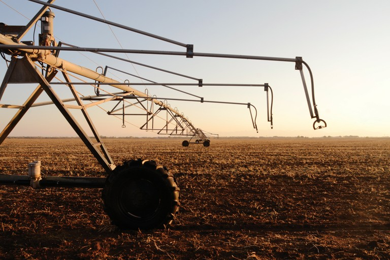 A center-pivot sprinkler stands unused over a field in Colorado's San Luis Valley.