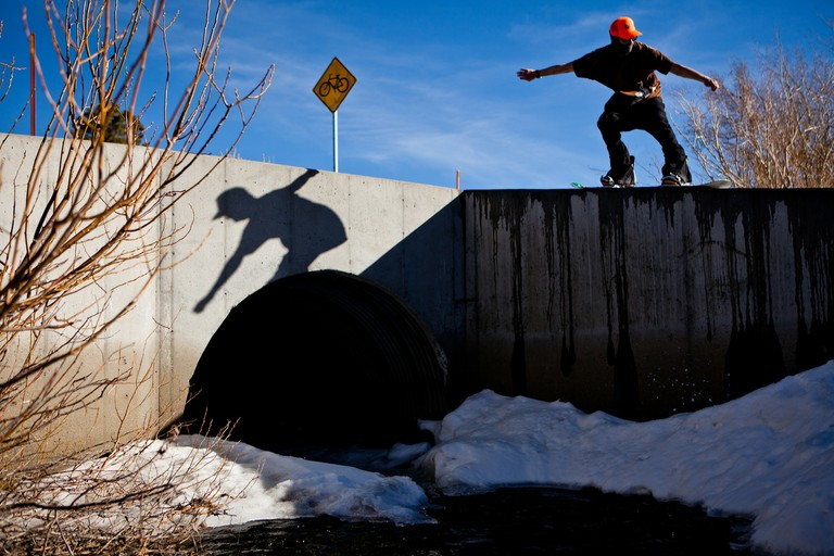 Ashley Mangels, a seasonal employee at Mammoth Mountain, grinds a concrete abutment in Mammoth Lakes, in early February -- height of the ski season.